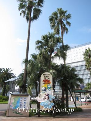 宮崎駅前。シュロの木と、「神々の国・高千穂」のモニュメント。